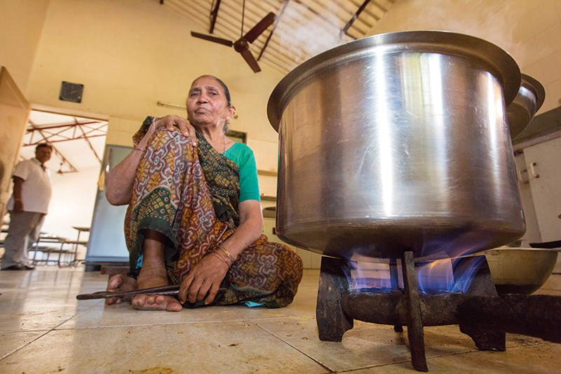 woman sitting next to gas stove