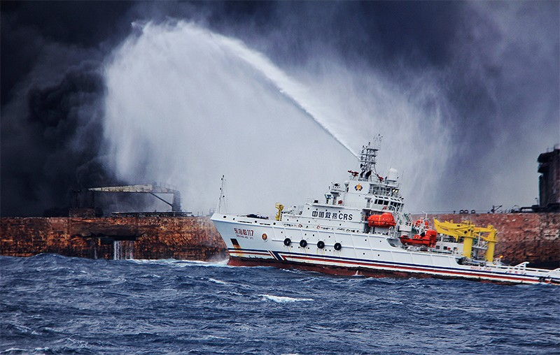 Rescuers spray foam to extinguish flames on the stricken oil tanker Sanchi