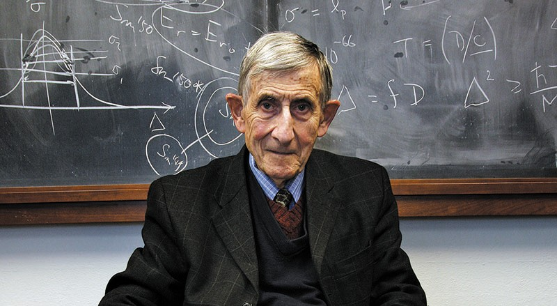 Freeman Dyson sits in front of a blackboard covered in mathematical notation