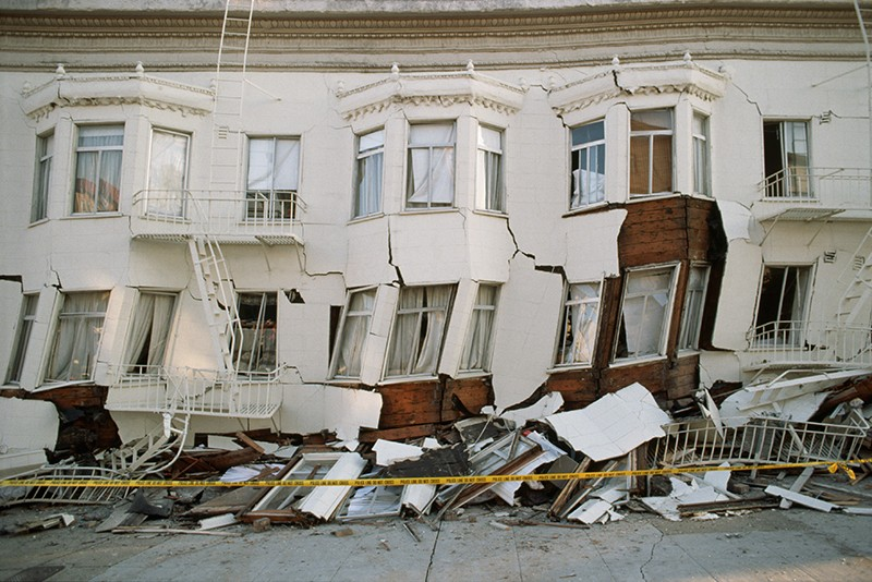 A row of buildings with cracked fronts, and piles of debris.