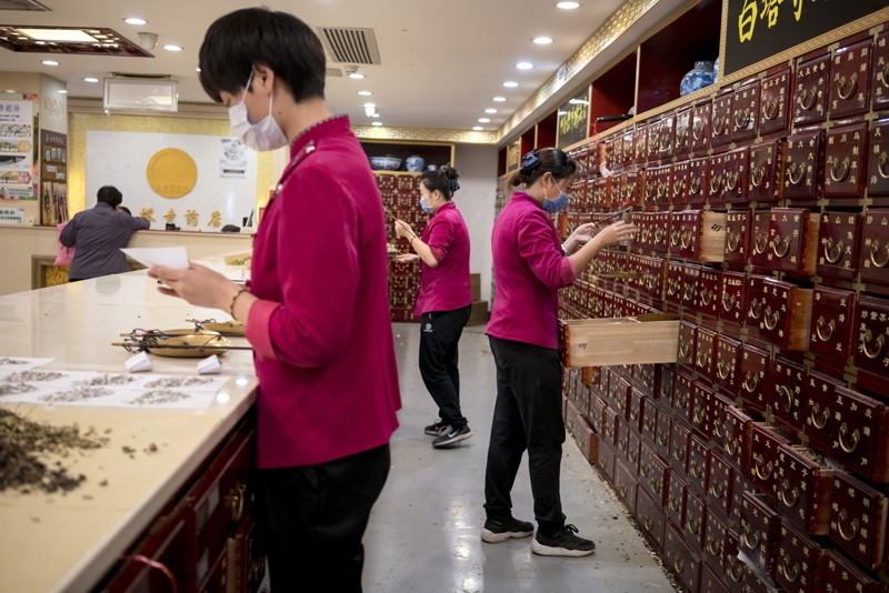 Employees prepare ingredients at a traditional Chinese medicine pharmacy