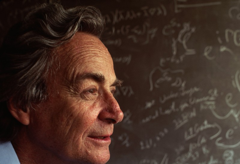 Richard Feynman stands in front of a blackboard strewn with notations in his Los Angeles Laboratory.