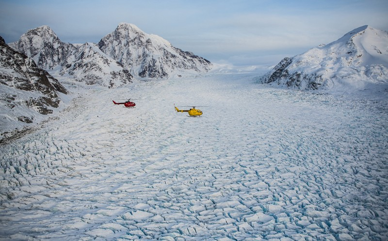Two helicopters fly over a huge glacier cared with rivulets and surrounded by a ring of mountains.