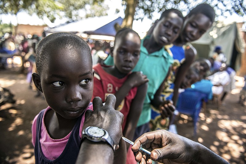 A girl receives her HPV vaccine in Ochaga, Uganda. There are a line of curious waiting children behind her.