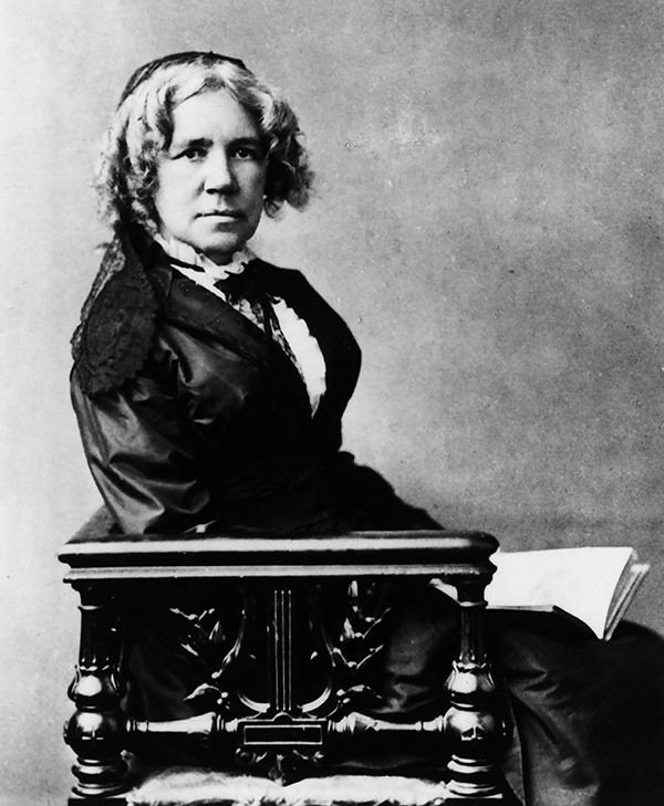 Undated portrait photograph of Maria Mitchell, seated, holding an open book.