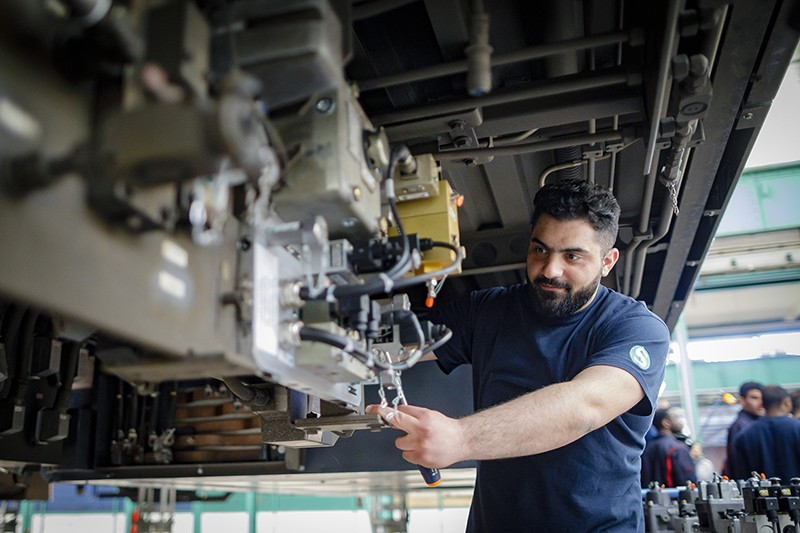 A Syrian man partakes in a training programme at a train repair facility in Berlin.