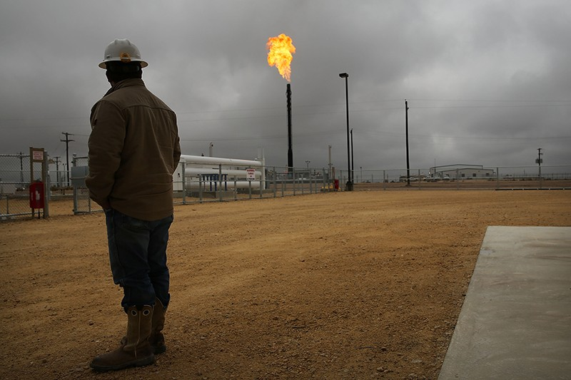 A man in a hard hat looks towards a natural gas flare at Deadwood natural gas plant under a cloudy sky in Texas, 2015.