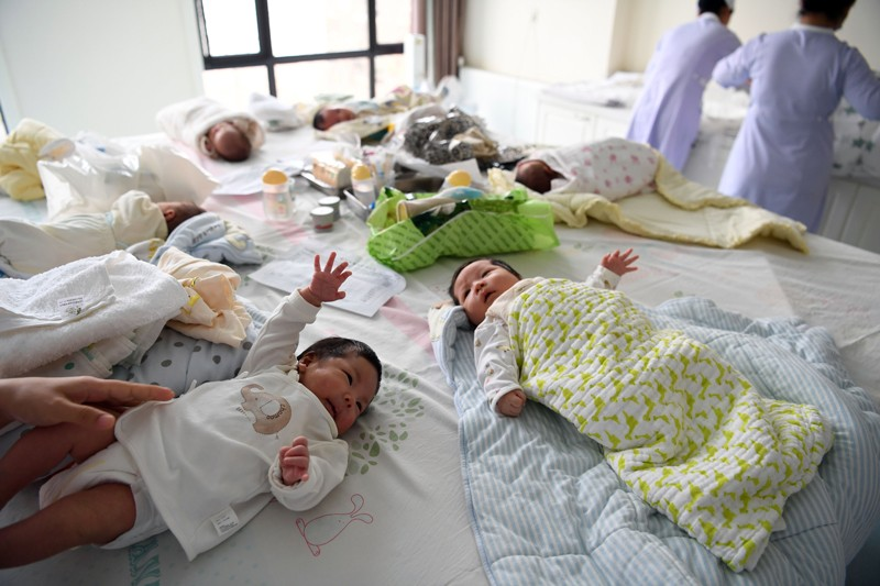 Staff members take care of babies in a postnatal confinement centre in Hefei, China