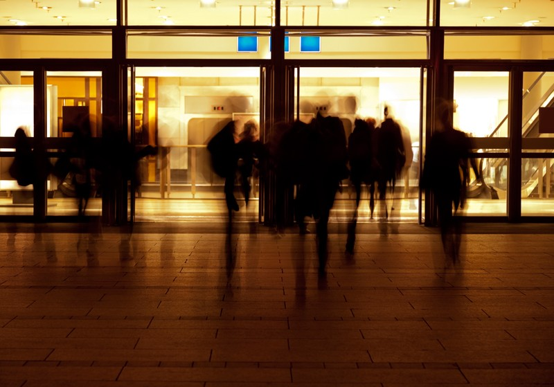 Silhouettes of people in front of building entrance at night.