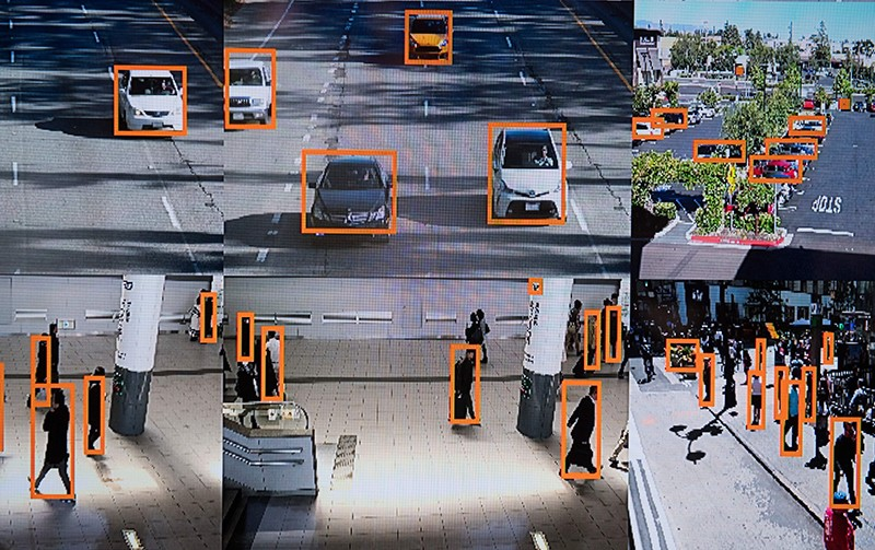 Multiple screens showcasing an AI vehicle and person recognition system. People and cars are outlined in orange boxes.