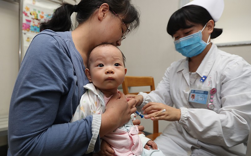 A baby stares past the camera as it is vaccinated at a hospital in Kunming, China in April 2018.