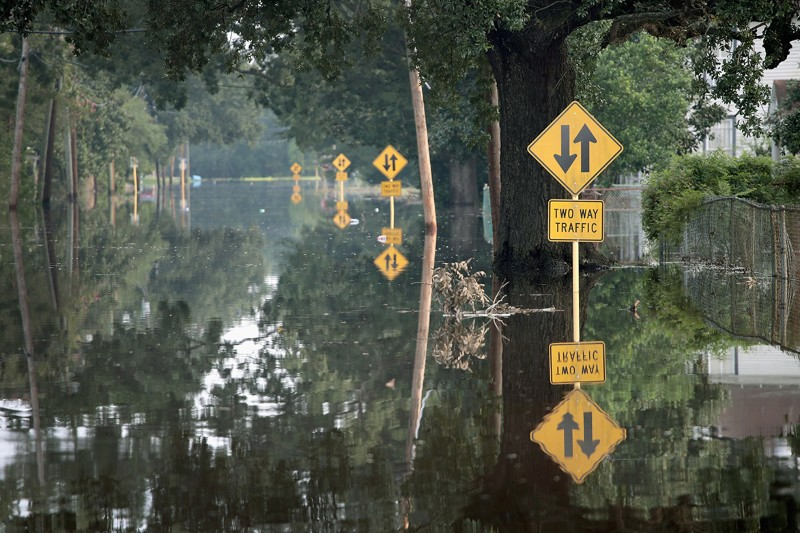 Half submerged traffic signs can be seen down a flooded street in Texas