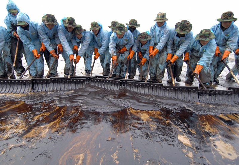 Members of the South Korean Army shovel up the oil from a beach
