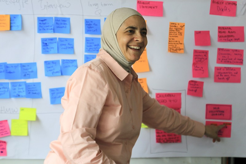 Rana Dajani smiling as she points during a brainstorming session. Behind her is a whiteboard covered with colourful postits