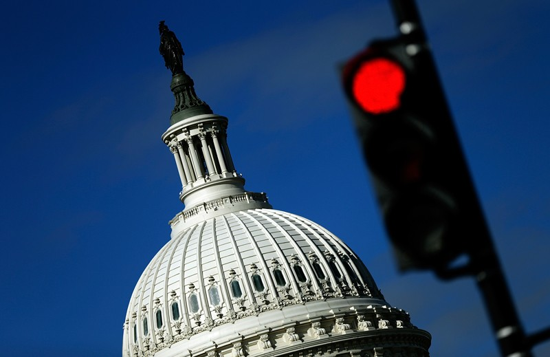 A red traffic light in front of the United States Capitol building