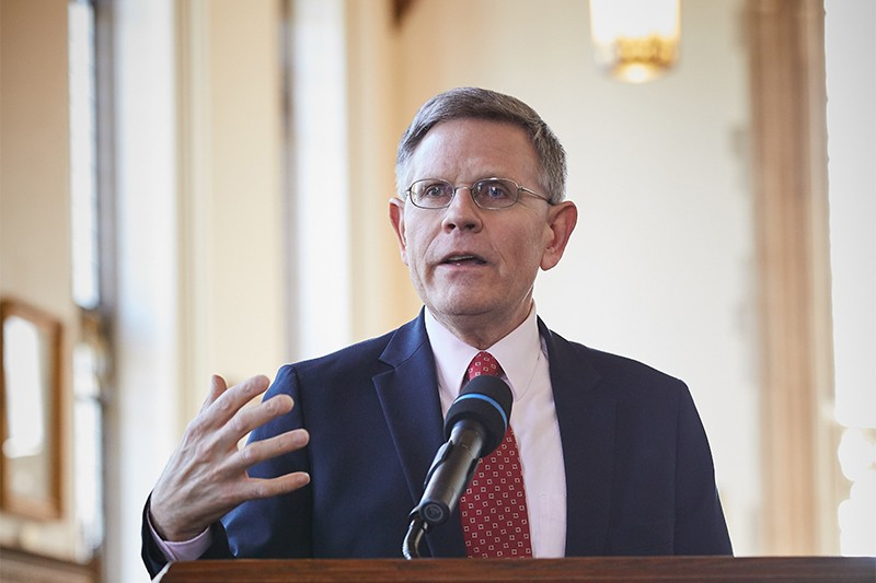 Droegemeier gestures as he speaks into a microphone on a podium in the Bizzell Library at Univ. Oaklahoma