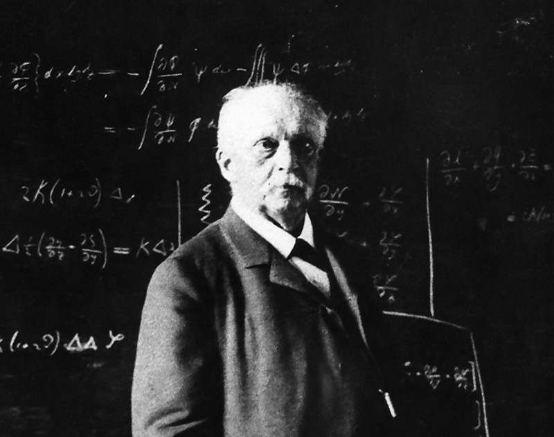 Hermann Helmholtz, suited in front of a whiteboard covered in equations, gazing off camera.