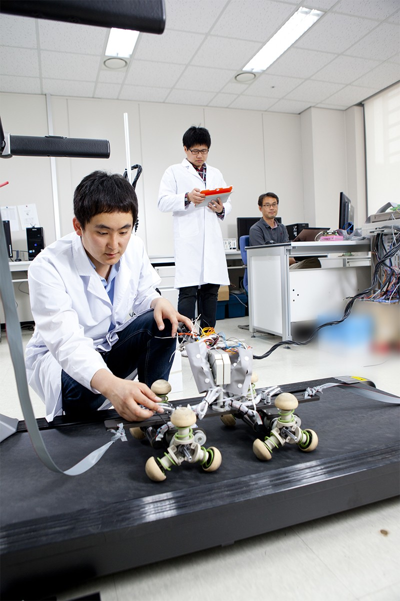 Photo of researcher with robot at Daegu Gyeongbuk Institute of Science and Technology, in South Korea