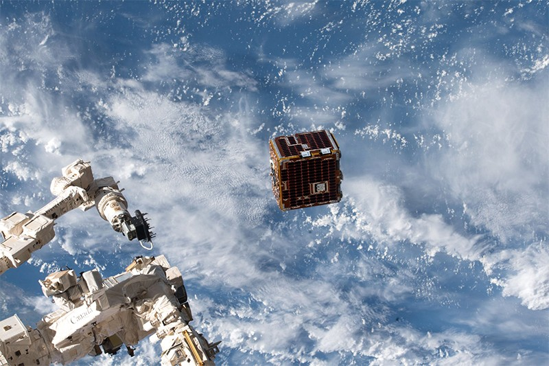 The Kaber Deployer (L) can be seen on the ISS as it deploys the RemoveDebris satellite (cube at centre) on June 20th. E