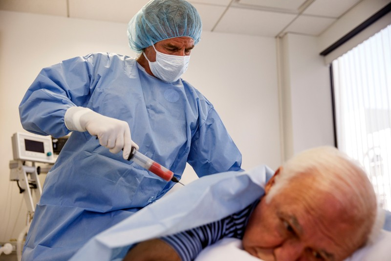 A doctor performs a procedure for stem cell therapy on a patient