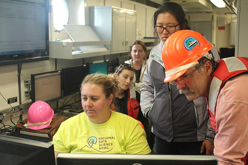 Marine biologist Kelly Robinson sits at a computer while members of her team look over her shoulder at the screen