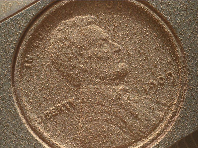 A coin loaded onto the Mars Curiosity rover covered in dust