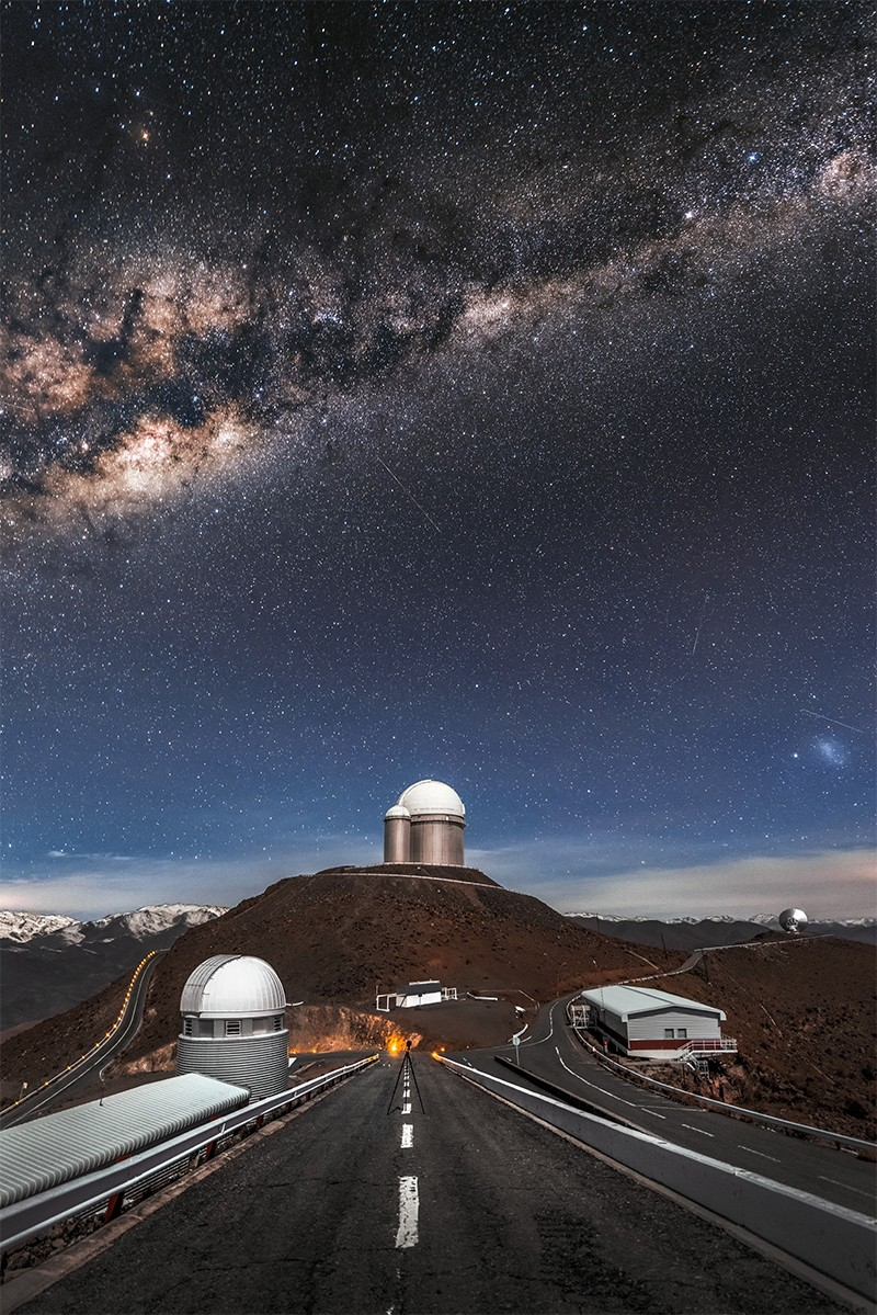 La Sille Observatory (c) seen from the end of a ramp/road. The milky way is visible in the sky above the observatories.