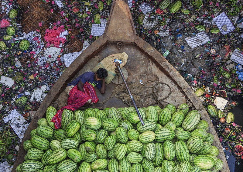 Aerial view of a man (left) resting on a boat full of watermelons (lower). The river is highly polluted and full of rubbish.