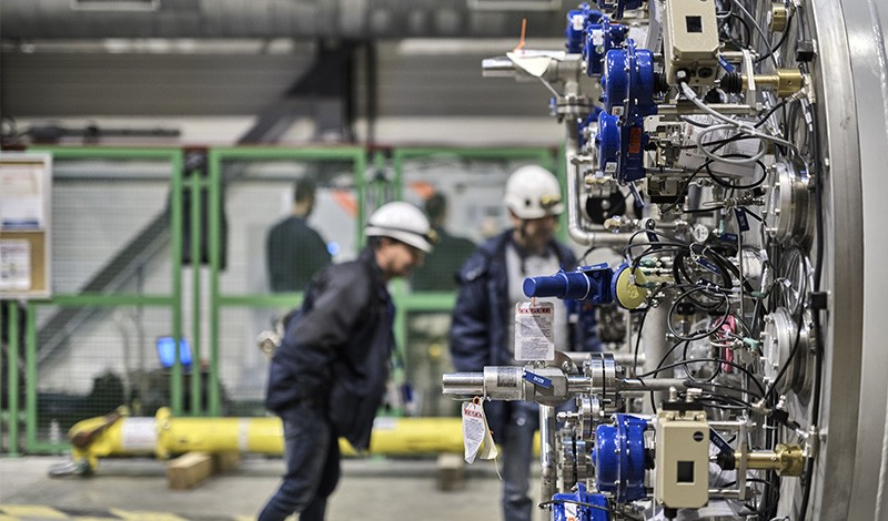 CLoseup of equipment at the LHC in CERN (r). In the background blurred figures can be seen examining the area