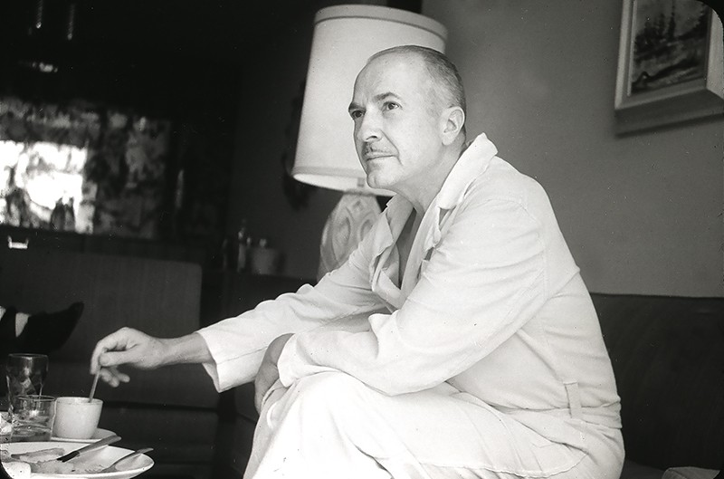 Robert Heinlein looks past the camera in his home. He is in a white dressing gown and is stirring a hot beverage.