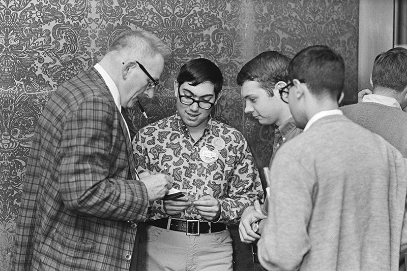 John W. Campbell (l) signs autographs for three fans .