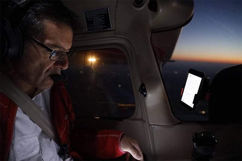 Wikelski (l) looks down at his tracking monitor in the cockpit of a cessna. A sunset can be seen through the window.