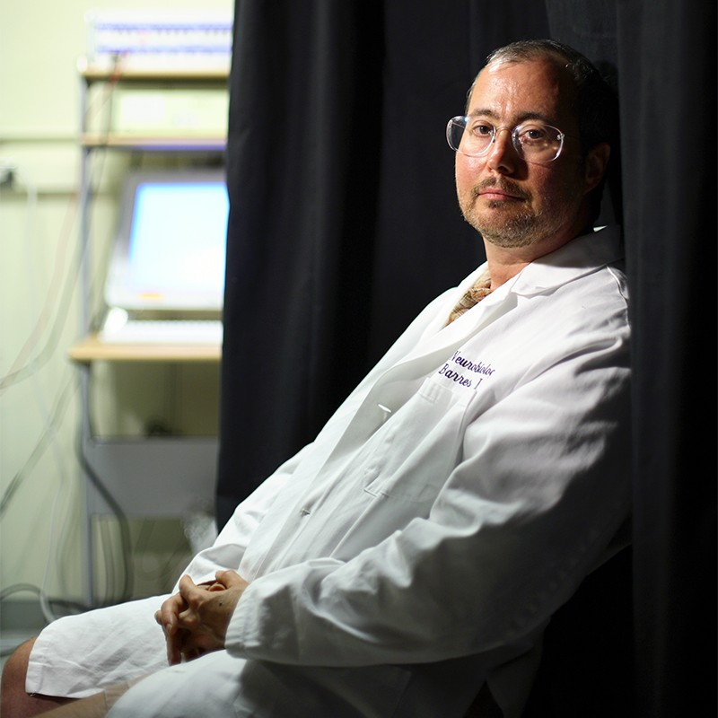 Ben Barres, seated in a lab coat, gazes out towards the camera.