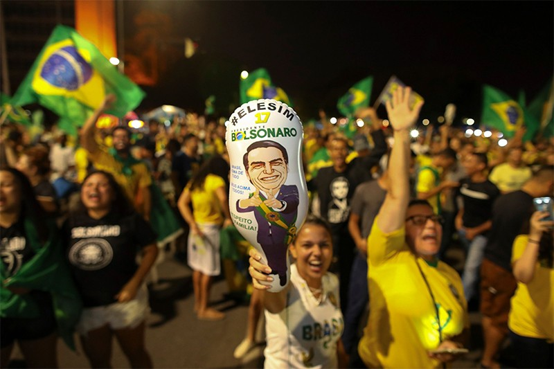 Bolsonaro supporters cheer and hold up balloons showing Bolsonaro's likeness after hearing the results