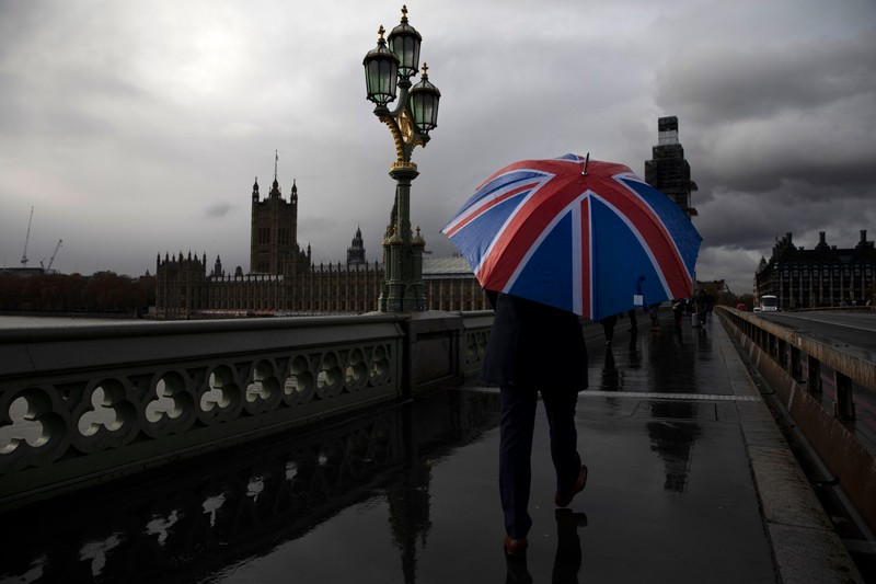 A man carries a Union Flag umbrella as he walks over Westminster Bridge