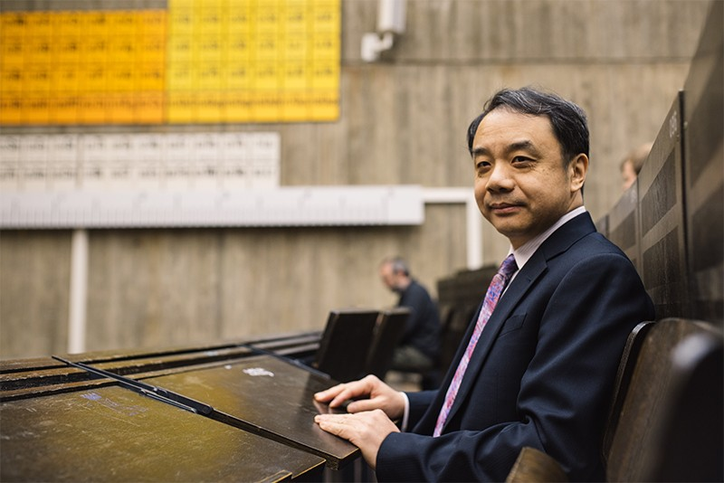 Prof. Wang Yifang sat in a lecture hall at Ruhr-Universitat Bochum. Periodic tables are visible on the walls behind him
