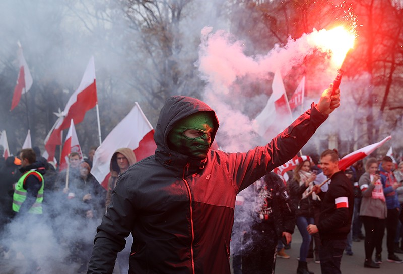 A protester in Poland holds a flare.