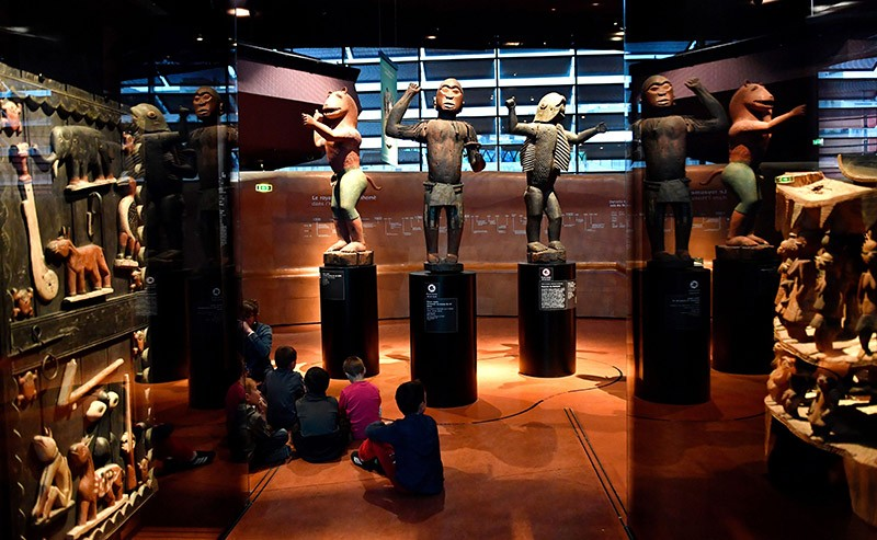 African statues on plinths in a Parisian museum, children sit on the floor looking at the exhibit.