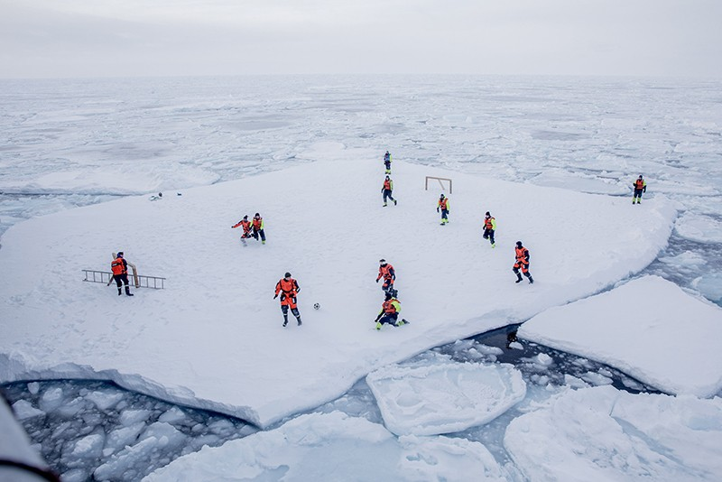 Scientists play football on the ice.
