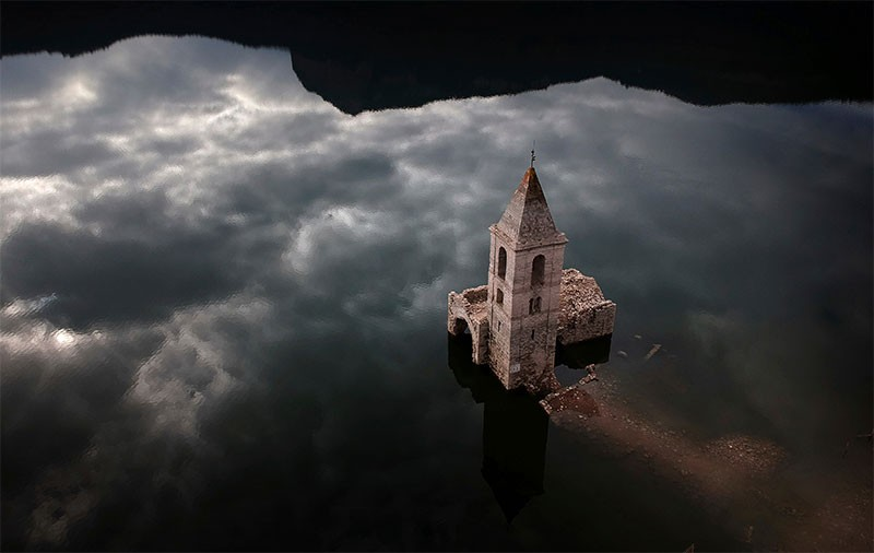 An 11th century village and church, which are usually covered by water, are partially exposed in a reservoir in Spain