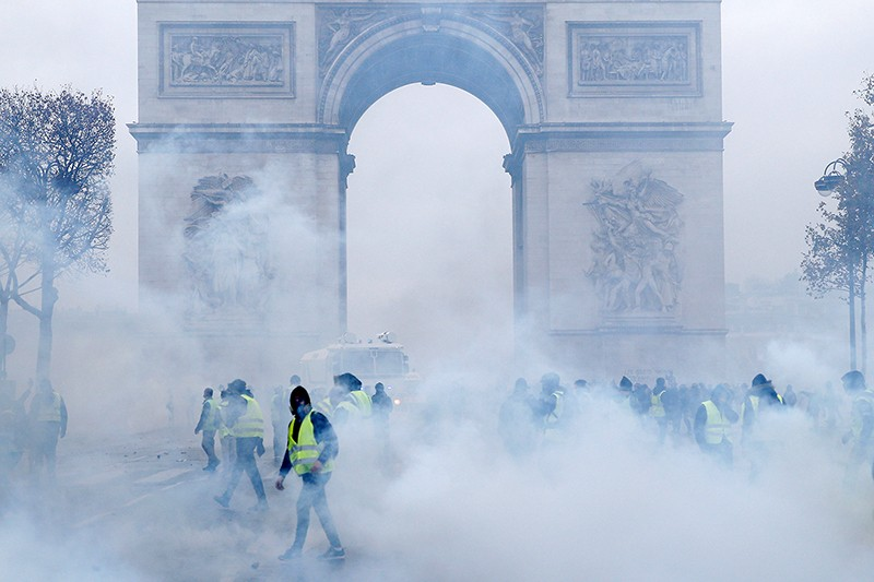 Protesters wearing yellow vests walk among tear gas