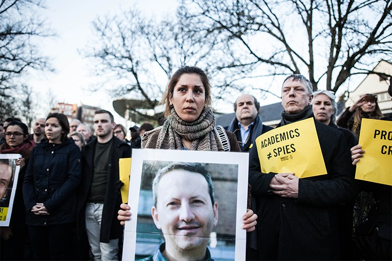 People protesting with photos of Ahmadreza Djalali nd and Hamid Babaei in Brussels
