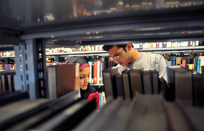 Students look at books between shelves in a university library in Cairo