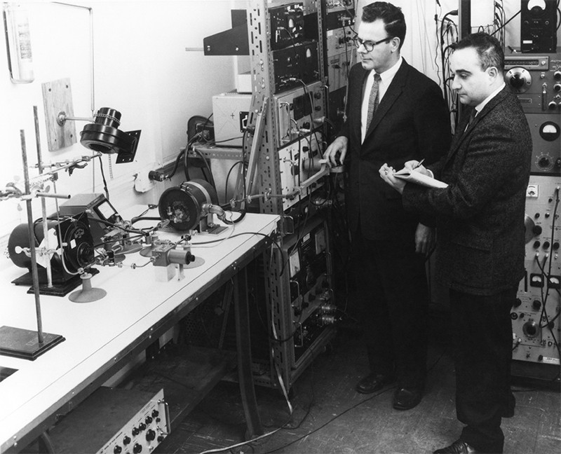 Black and white photo of US physicist Gordon Gould (c) and Ben Senitsky (r) workingwith masers at TRG labs in the 1950s.