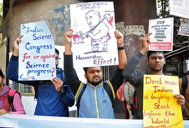 People hold signs to protest comments made at the Indian Science Congress