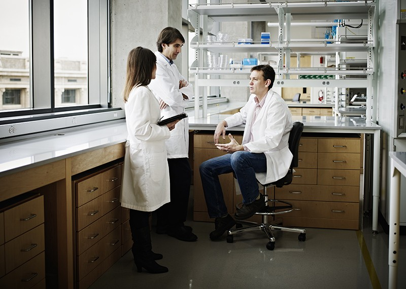Scientists in research laboratory discussing project