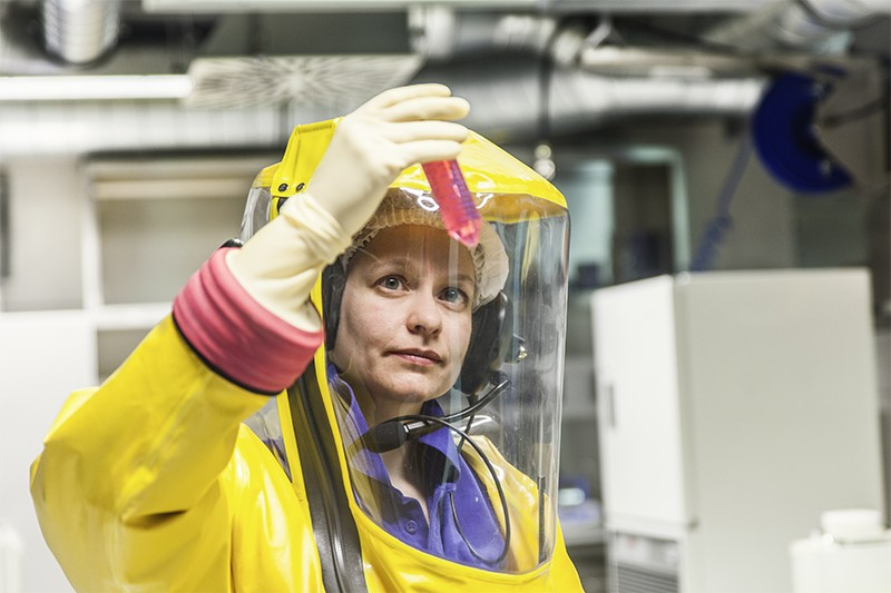 A worker in protective gear examines a vial at a BSL-4 lab in Germany.