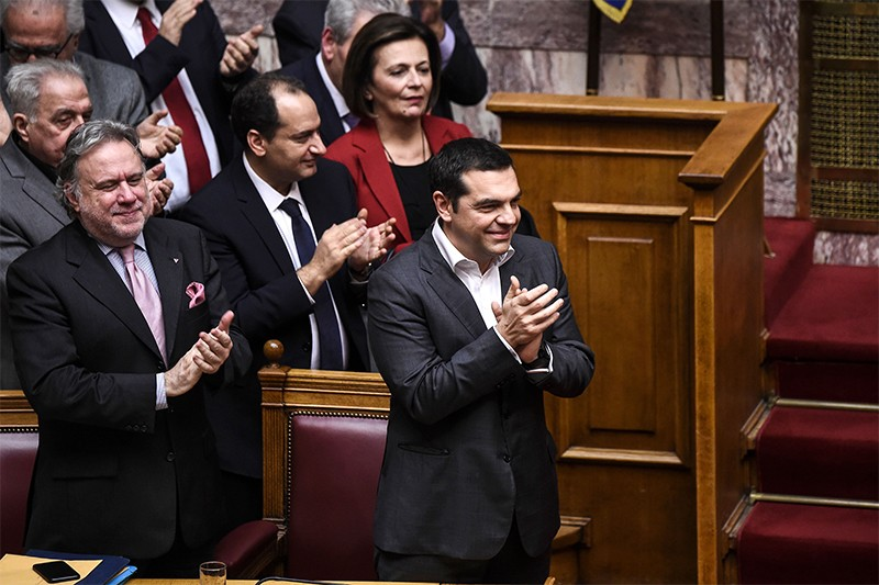 Greece's Prime Minister Alexis Tsipras celebrates with other gov. members after a voting session on the Prespa Agreement
