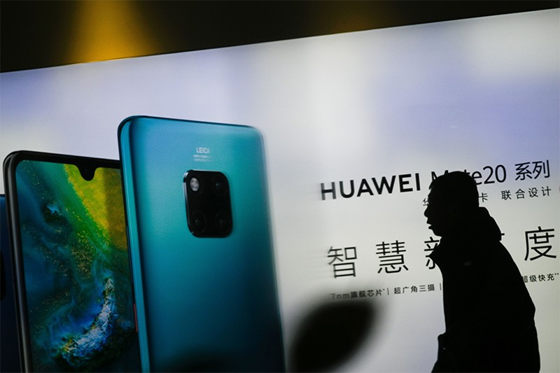 A man in dark profile walks past Huawei advertising outside a store in Beijing on January 29, 2019.