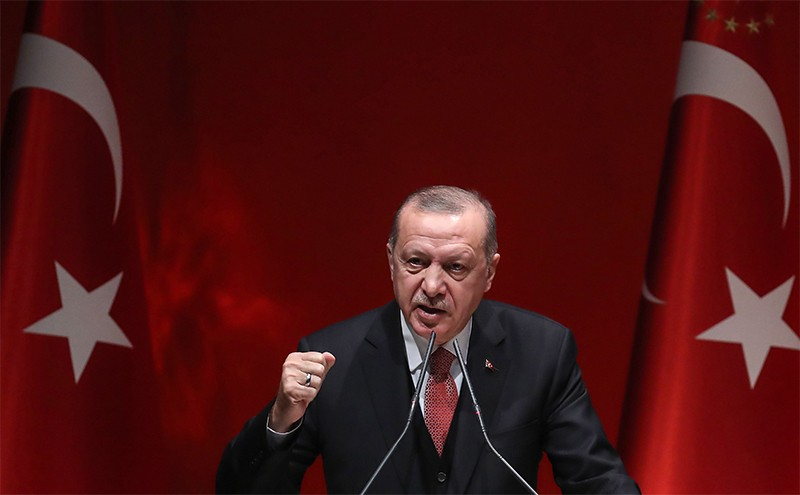 Turkish President Erdoğan speaks at a podium in 2019, with Turkey's national flag in the background.